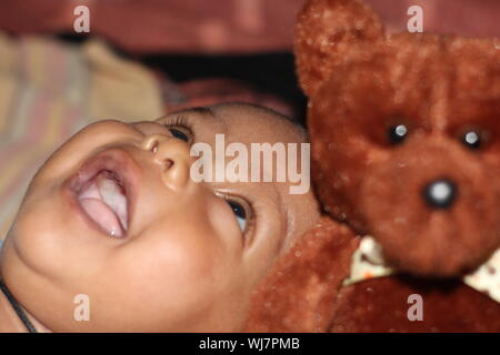 Cute Baby Looking Up With Teddy Bear - Stock Photo