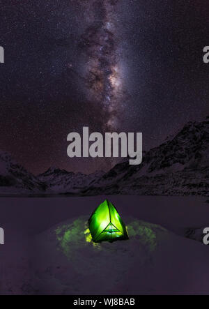 High Angle View Of Illuminated Tent On Snow Covered Field Against Starry Sky - Stock Photo
