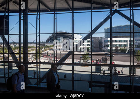 LYON, FRANCE - JULY 13, 2019: Passengers passing by the terminal 1 of Aeroport de Lyon Airport, Saint Exupery, while the iconic train station of the a - Stock Photo