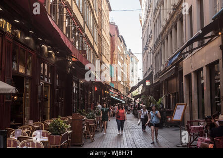 LYON, FRANCE - JULY 13, 2019: Tourists walking in Typical street of the Vieux Lyon (old Lyon) on the Presqu'ile district with tourists passing by near - Stock Photo