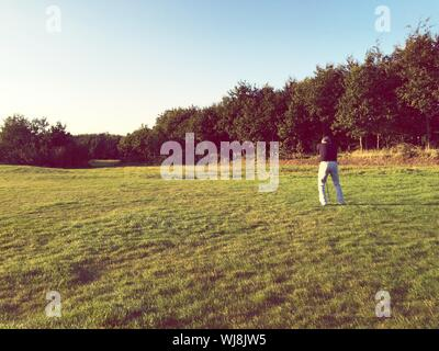 Rear View Of Man Playing Golf Against Sky - Stock Photo