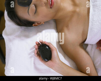 Woman Having Lastone Therapy While Lying On Massage Table - Stock Photo