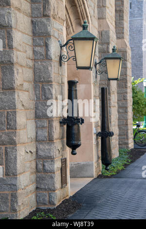 West Point, New York - August 30, 2019: Cannon barrels are seen mounted to the stone wall near the door of an historic building on the campus of the W - Stock Photo