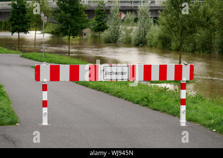 Warning Sign On Road In Flooded Area - Stock Photo