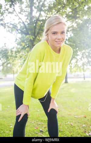 Active smiling blonde pausing after a run in a park on a sunny day - Stock Photo