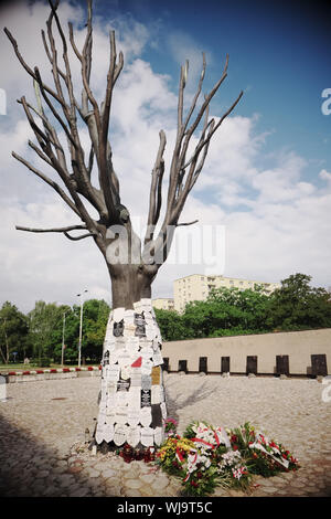 Warsaw Poland - Pawiak prison with a memorial tree to the victims of German Nazis terror and torture during WW2 - Stock Photo