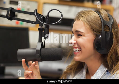 Laughing pretty radio host moderating sitting in studio at college - Stock Photo