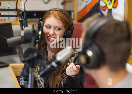 Attractive happy radio host interviewing a guest in studio at college - Stock Photo