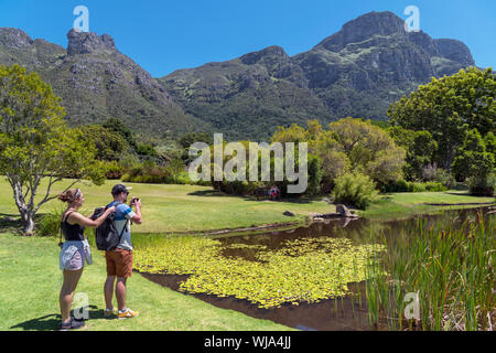 Young couple taking photos of pond in Kirstenbosch National Botanical Garden looking towards eastern face of Table Mountain, Cape Town, South Africa - Stock Photo