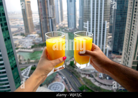 Female and male hands hold glasses of fresh cold orange juice with city skyscrapers view of modern city Dubai. Two glasses of orange juice on cityscap - Stock Photo