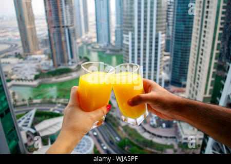 Female and male hands cheer glasses of fresh cold orange juice with city skyscrapers view of modern city Dubai. Two glasses of orange juice on citysca - Stock Photo
