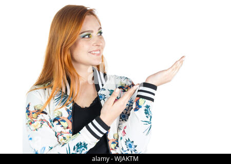 Friendly girl uses both hands to present the empty space for advertising. Redhead girl wears a jacket with floral patterns. Summer and tropical. White - Stock Photo