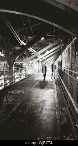 Rear View Of Silhouette People Walking On Bridge At Night - Stock Photo