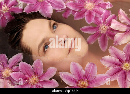 Close-up Of Young Woman With Flowers In Bathtub - Stock Photo