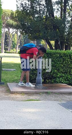 Side View Of Boy Drinking Water From Fountain Against Plants In Park - Stock Photo