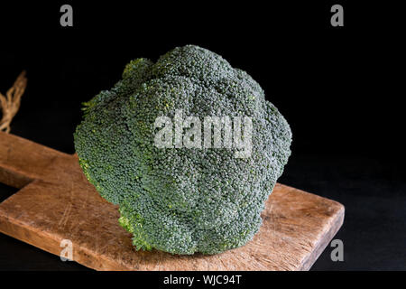 Fresh broccoli on a cutting board on a black background, rustic style, dark key. Healthy food, close up - Stock Photo