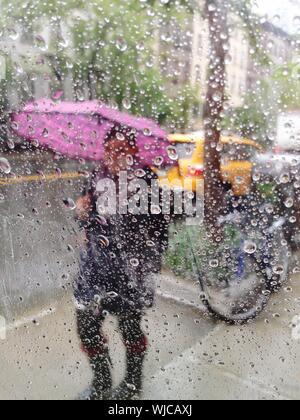 Woman With Umbrella On Street In Rain Seen Through Wet Window - Stock Photo