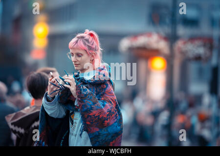 Girl looking at her smart phone, Menningarnott or Cultural day, Reykjavik, Iceland. - Stock Photo