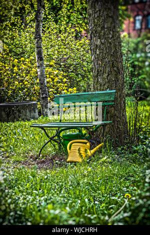 garden bench with yellow ewer. - Stock Photo