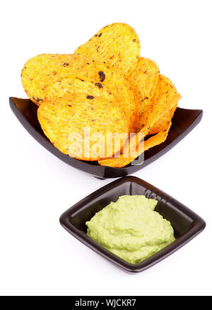 Arrangement of Tortilla Chips and Guacamole Sauce in Black Bowls isolated on White background - Stock Photo