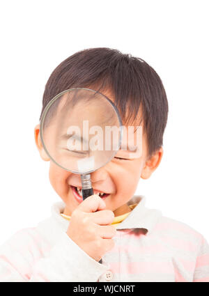 asian boy holding magnifier and close eyes - Stock Photo