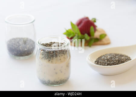 Detox and healthy superfoods breakfast concept: chia pudding. Vegan almond milk with chia seeds on a white table with strawberry - Stock Photo