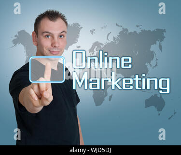 Young man press digital Online Marketing button on interface in front of him - Stock Photo