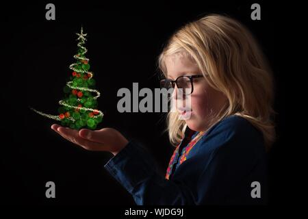 Digital Composite Image Of Cute Girl With Christmas Tree On Palm Against Black Background - Stock Photo