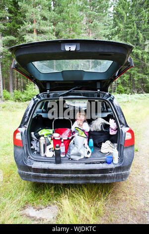 Young girl sit in the back of a car eating - Stock Photo