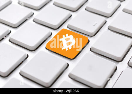 Selective focus on bitcoin button in the middle of keyboard - Stock Photo