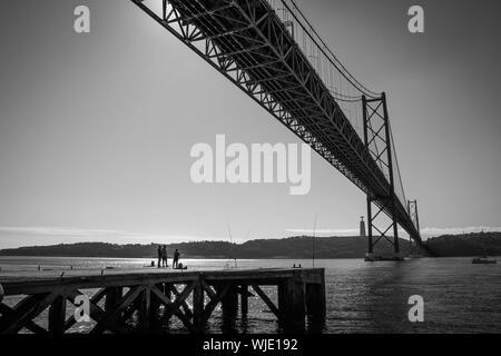 Distant View Of Men On Pier At Tagus River Below April 25th Bridge - Stock Photo
