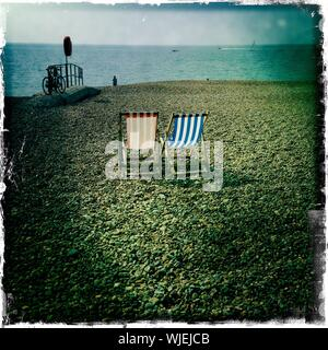 Two Deck Chairs On Beach