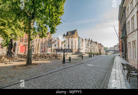 Cobblestone street, the Jan Van Eyck Monument and square, and rows of historic houses on either side of a canal in Bruges, Belgium - Stock Photo