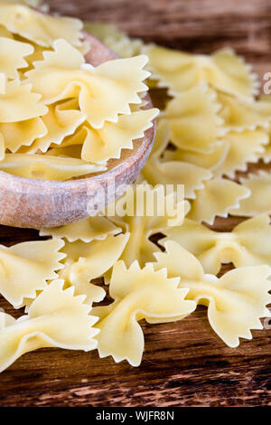 uncooked pasta in wooden spoon closeup on wooden background - Stock Photo