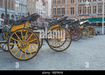 Yellow carriages and carriage wheels in a row, in the center of the historical city of Bruges, Belgium - Stock Photo