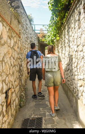 ISLE OF CAPRI, ITALY - AUGUST 2019: People walking on the narrow uphill path which leads from the port on the Isle of Capri to Capri town. - Stock Photo