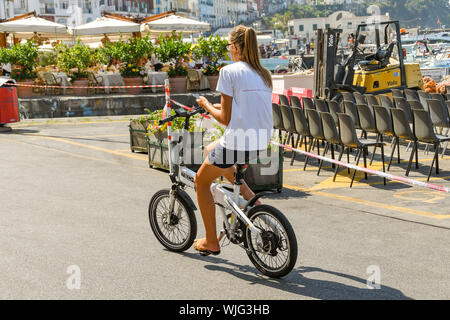 ISLE OF CAPRI, ITALY - AUGUST 2019: Person riding an electric bike in the port on the Isle of Capri. She is operating a mobile phone while cycling. - Stock Photo
