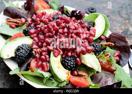 A healthy salad with pomegranate, avocado, tomatoes, almonds and argula lettuce over a rustic background. Stock Photo