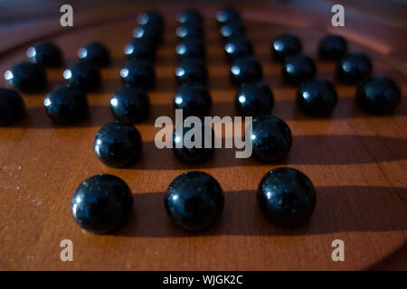 Close-up Of Black Marbles On Chinese Checkers Board - Stock Photo