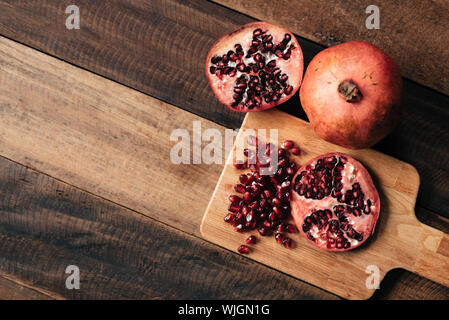 Close-up Of Pomegranates On Wooden Table - Stock Photo