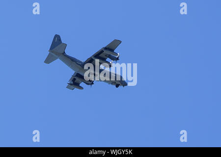 grey military transport plane fly on blue sky background - Stock Photo