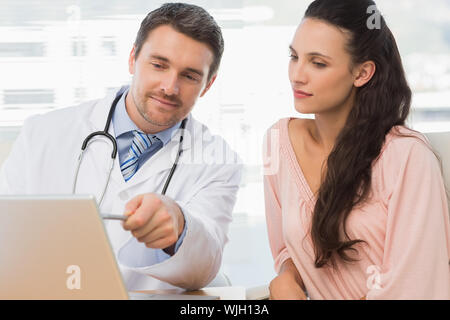 Male doctor showing something on laptop to patient in medical office - Stock Photo