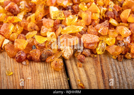 Small raw amber on a wooden table. A precious find from the coast of Central Europe. Light background. - Stock Photo