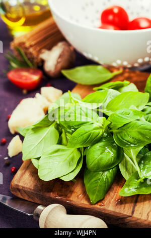 Basil and ingredients for making italian pasta - Stock Photo