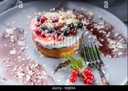 Close-up redcurrant, blueberry tart dessert with cream and almonds on a dark plate - Stock Photo