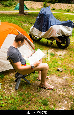 Side View Of Man Sitting On Chair By Tent At Forest - Stock Photo