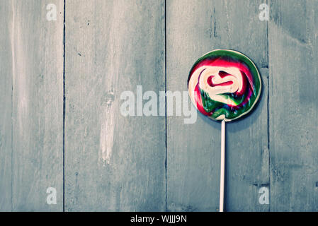 Photo of red and green lillipop on wooden background - Stock Photo