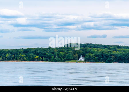 People walk on the beach in front of the Old Mission Point Lighthouse on Old Mission Peninsula near Traverse City, Michigan, as viewed from the water. - Stock Photo