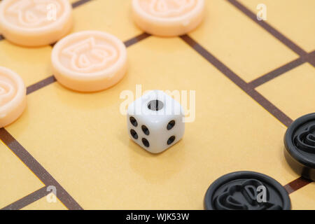 High Angle View Of Dice And Coins On Checkers Board - Stock Photo