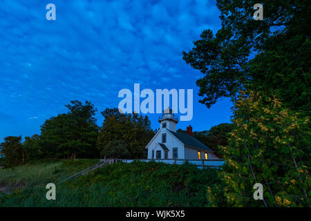 Old Mission Point Lighthouse at twilight showing lights in windows, at the 45th parallel on Old Mission Peninsula, Traverse City, Michigan. - Stock Photo